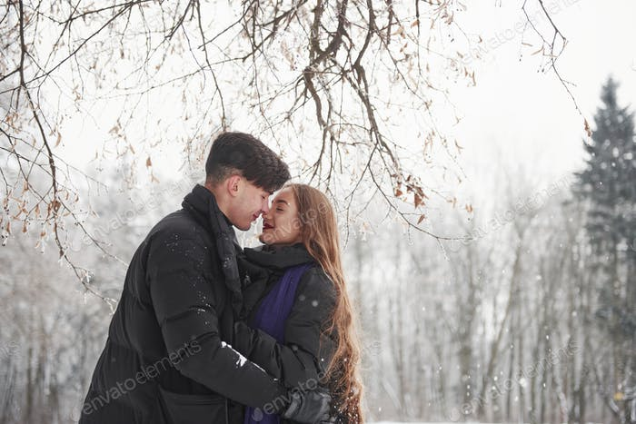 Satisfaction on their faces. Gorgeous young couple have good time together in snowy forest