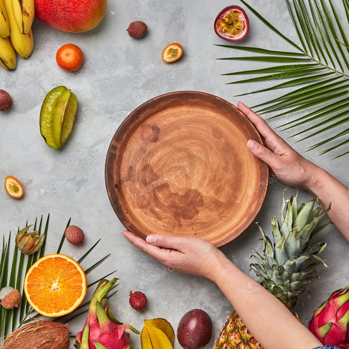Thumbnail for Hands of a woman holding a brown empty plate around a different tropical fruit ripe on a gray