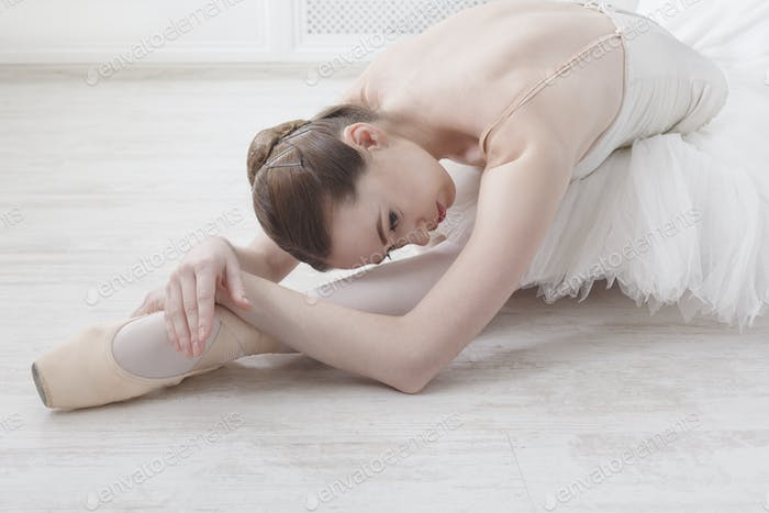 Graceful Ballerina stretching, ballet background