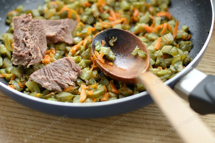 Frying pan with beef carrot and greens