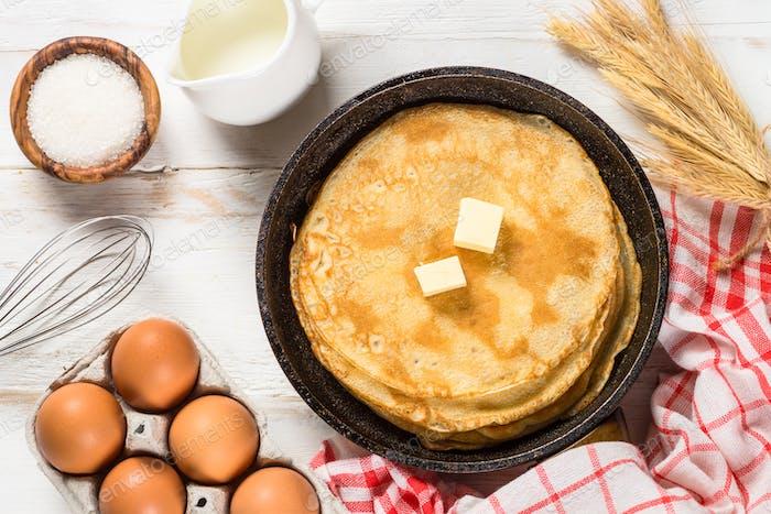 Crepes oder dünne Pfannkuchen in der Pfanne mit Zutaten zum Kochen