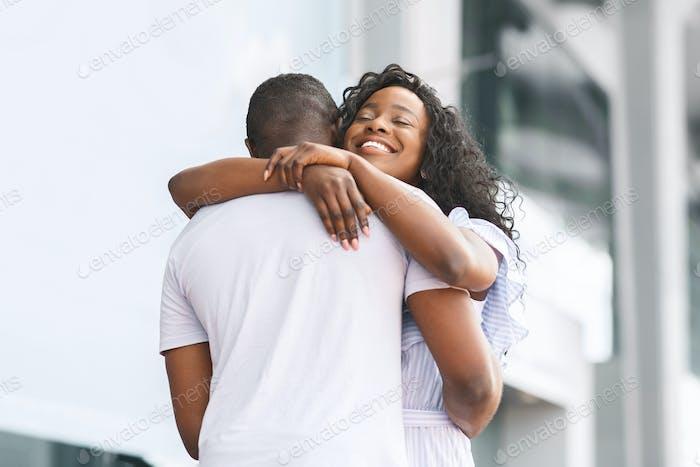 Happy african woman embracing her loving boyfriend