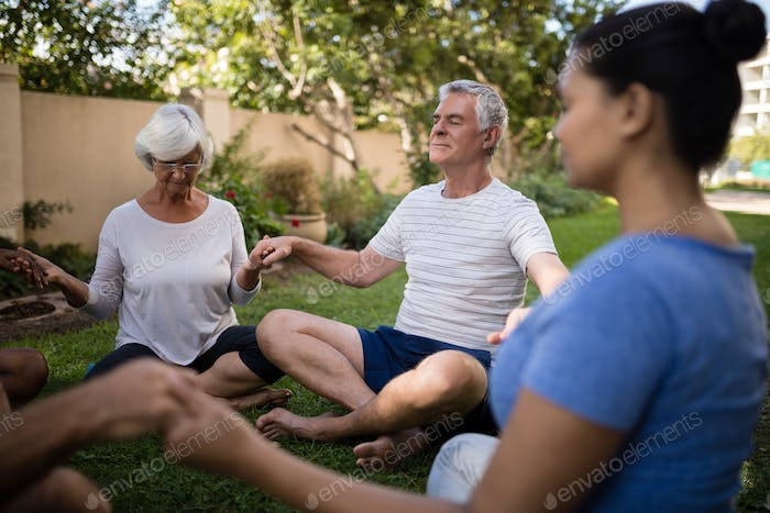 Senior people holding hands and meditating with trainer