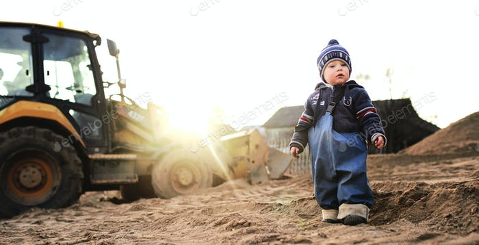 A boy in the village on the background of a tractor walks on the sand .