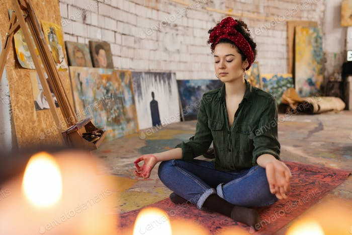 Young thoughtful woman with closing eyes sitting on yoga mat in