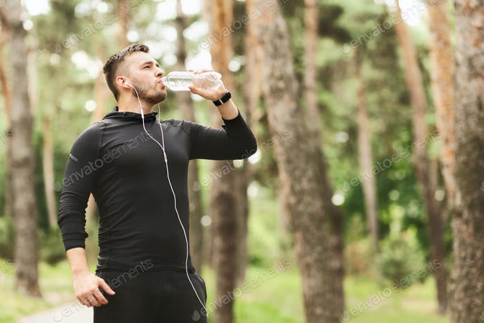Young athletic man drinking water after training in city park