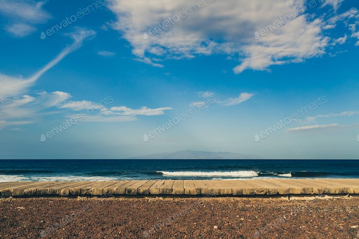 Inspirational landscape, wooden sidewalk on beach, Tenerife coas