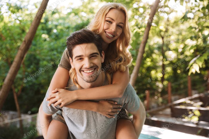 Happy young man carrying his pretty girlfriend on his back