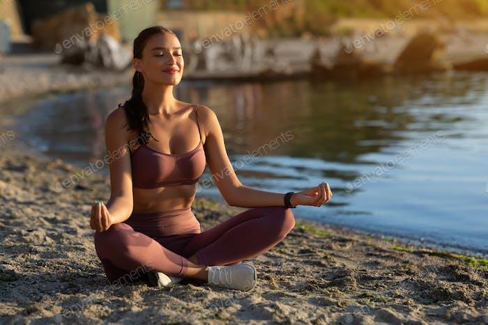Ruhige weibliche Yogi sitzen in Lotuspose und meditieren