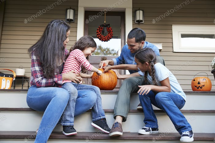 Family Carving Halloween Pumpkin On House Steps