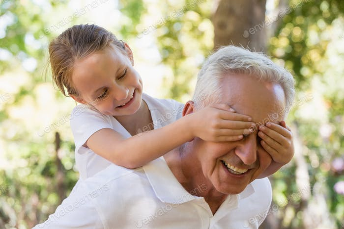 Girl covering his grandpa's eyes in the forest