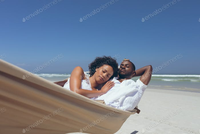 Front view of romantic young multi-ethnic couple relaxing on hammock at beach on sunny day