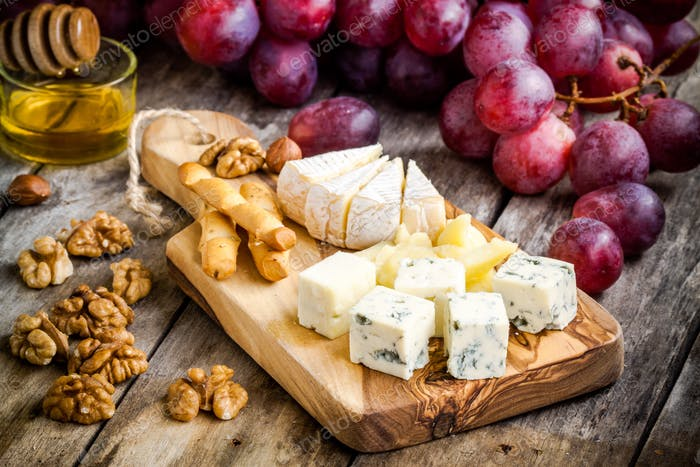 Thumbnail for Cheese plate: Camembert, Parmesan, blue cheese, bread sticks, walnuts, hazelnuts, honey, grapes
