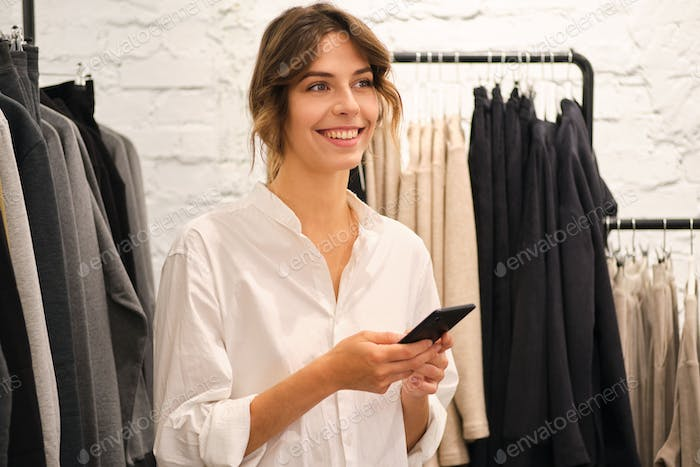 Young pretty woman happily using cellphone working in fashion showroom