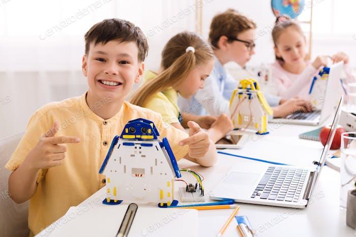 Der kluge Junge zeigt seinen Roboter. Stolzer Student seines Projekts