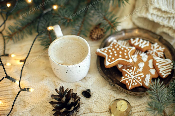 Christmas gingerbread cookies, warm coffee, fir branches and warm lights on cozy knitted background