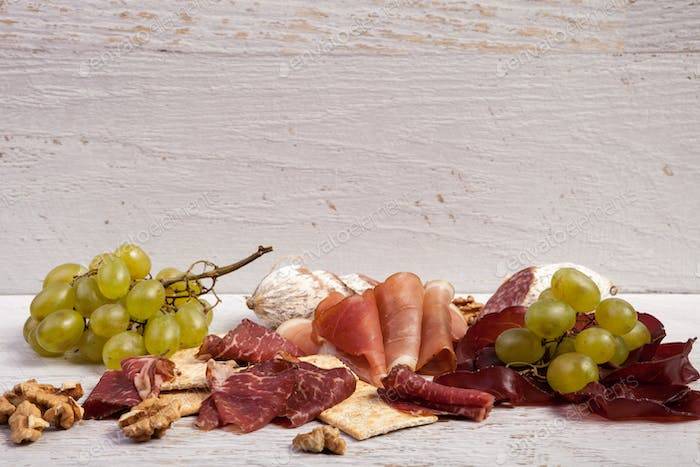 Mixed antipasto from grape, crackers and ham