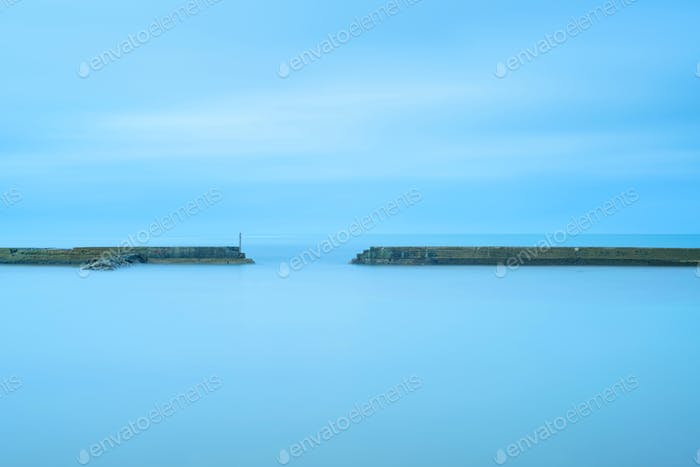 Concrete pier and stairs in a cloudy and blue ocean