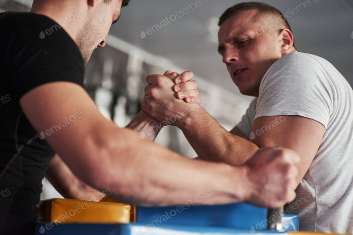 All forces to overcome the enemy. Arm wrestling challenge between two men. Match on a special table