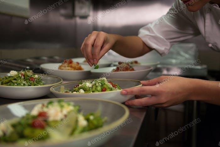 Female chef garnishing appetizer plates at order station