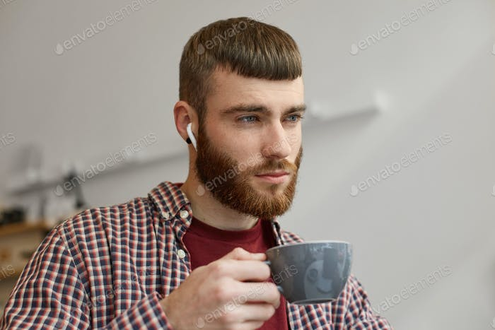 Photo of young attractive ginger bearded man holding a gray coffee cup, think about something