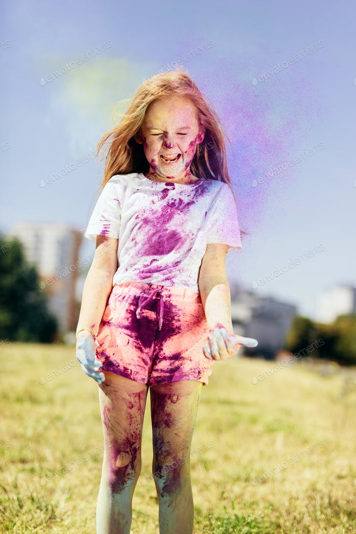 Little girl playing with holi powder outdoors