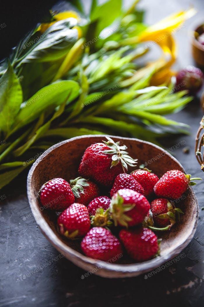 Köstliche Erdbeeren mit gelben Blüten auf einem grauen Hintergrund in einem Vintage-Kranz. Gesunde Ernährung