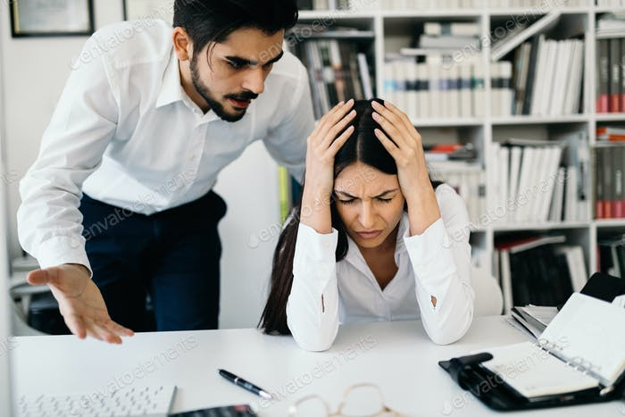 Businessman yelling at female colleague in office