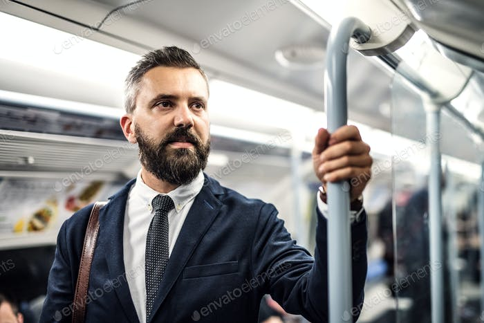 A portrait of a serious hipster businessman travelling by subway.