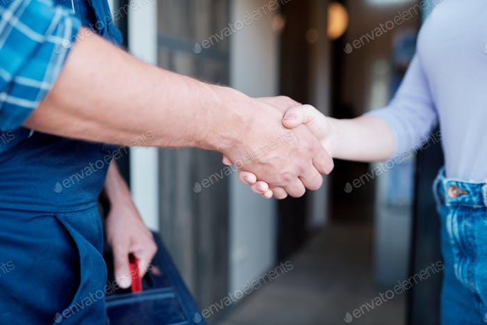 Young woman shaking hand of master while repairman leaving