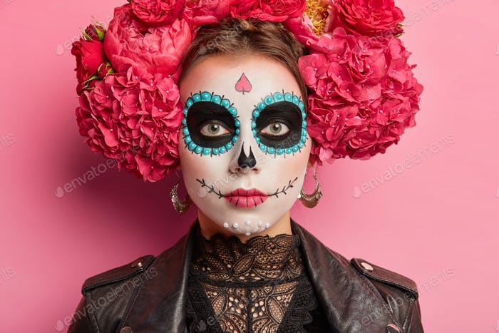 Close up shot of serious woman catrina celebrates halloween or day of death wears peonies wreath and