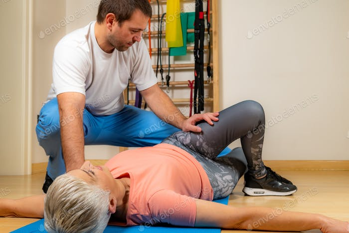 Physiotherapist Stretching Senior Woman