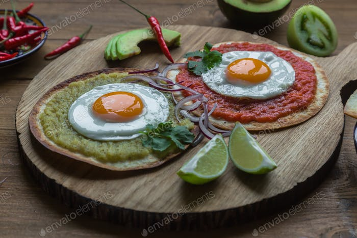Variety of colorful mexican cuisine breakfast dishes on a wooden table