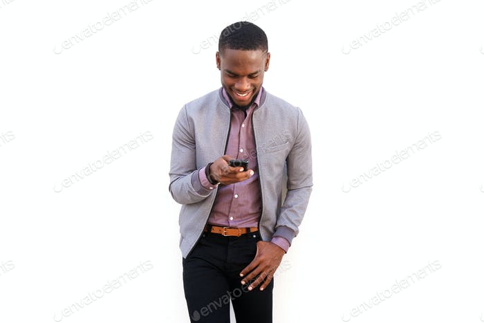 Happy young black man sending text message