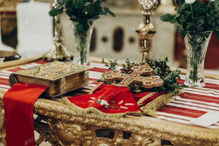 goldene Bibel und Kreuz auf Altar in der Kirche