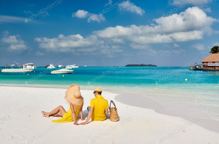 Couple in yellow on tropical beach at Maldives