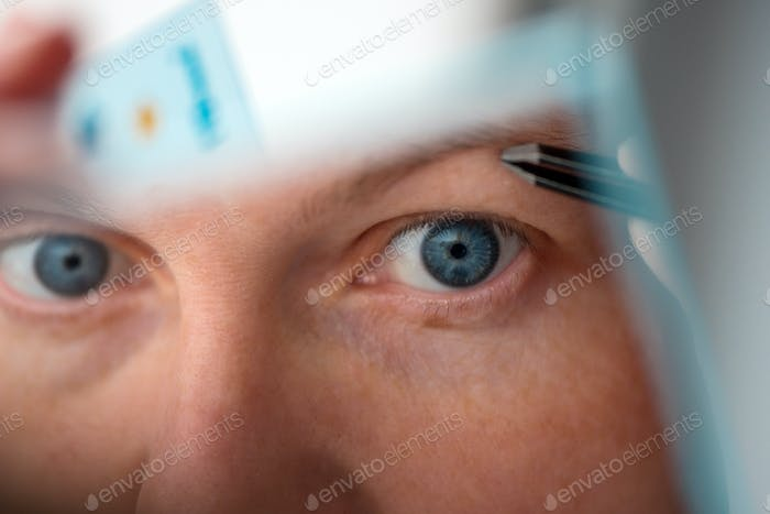 Woman plucking eyebrows by the window