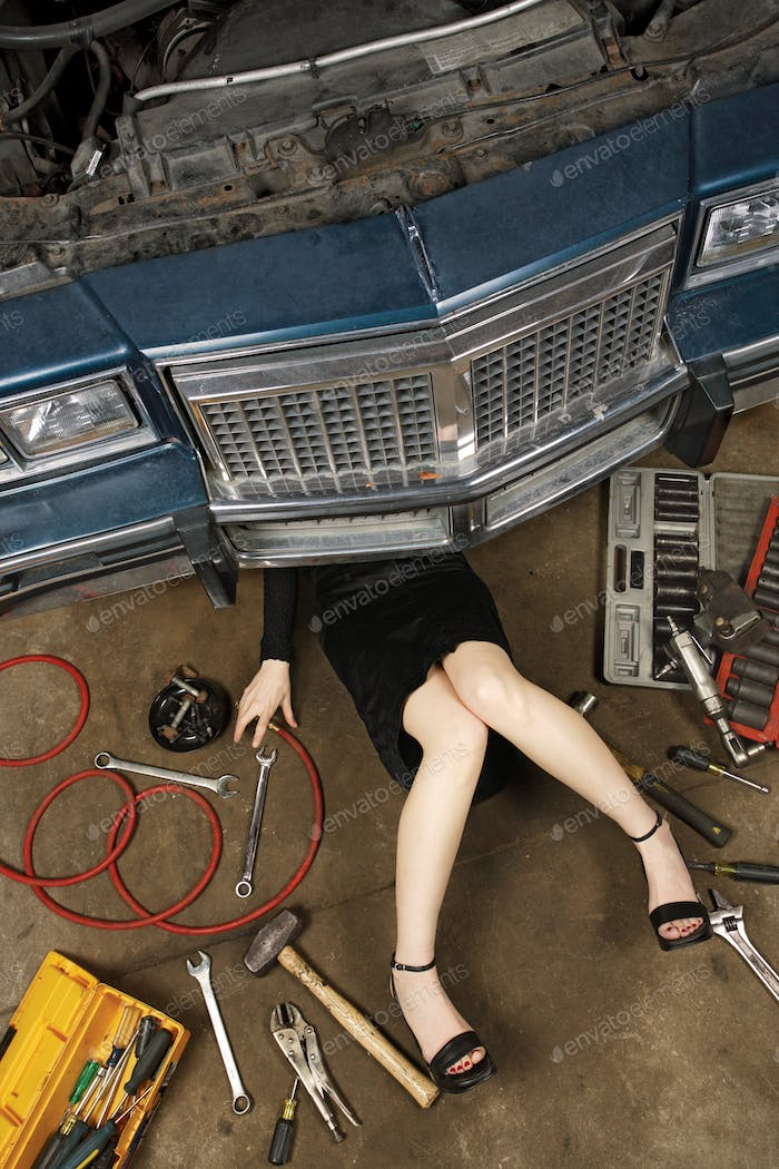 female fixing her car