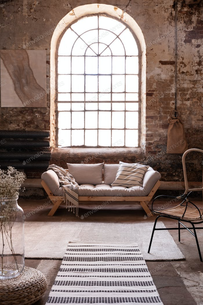 Fenster über grauem Holzsofa im geräumigen Wohnzimmer Interieur