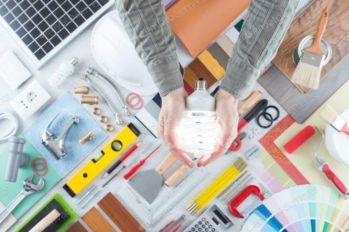 Mann hält eine CFL Energiesparlampe