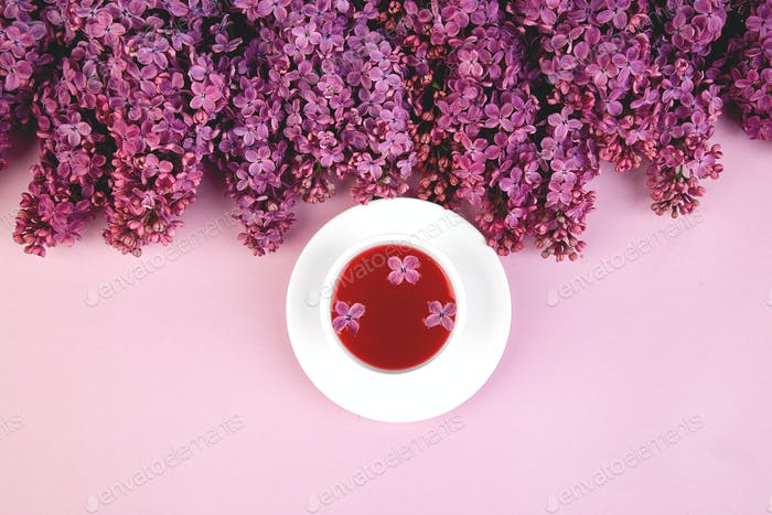 Cup of tea and branches of flowers bouquet blooming lilac