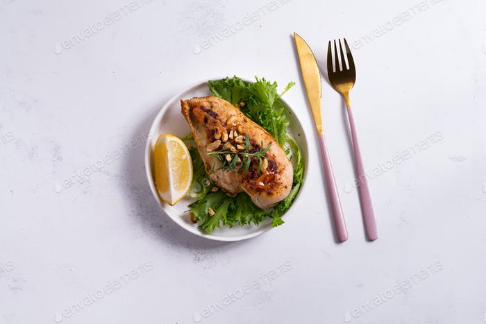 grilled chicken breast fillet with asparagus and lemon in slate plate and white stone background