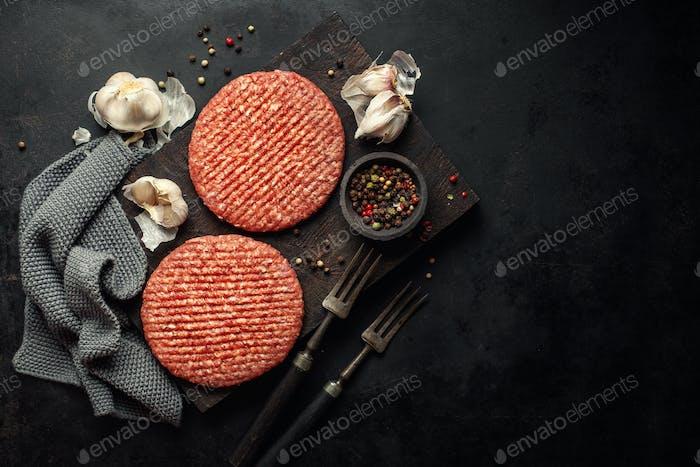 Raw burger meat on board