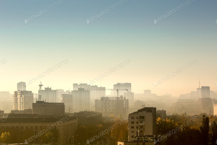 Cityscape at sunrise, building rooftops, bird view