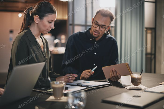 Two young businesspeople going over paperwork at an office table