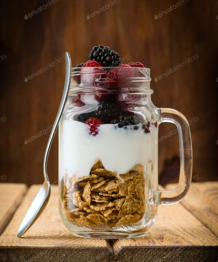 jug with berries cerealas  and yogurt on wood