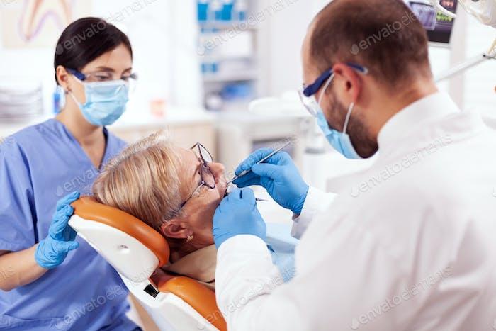 Stomatolog and nurse treats teeth of senior woman