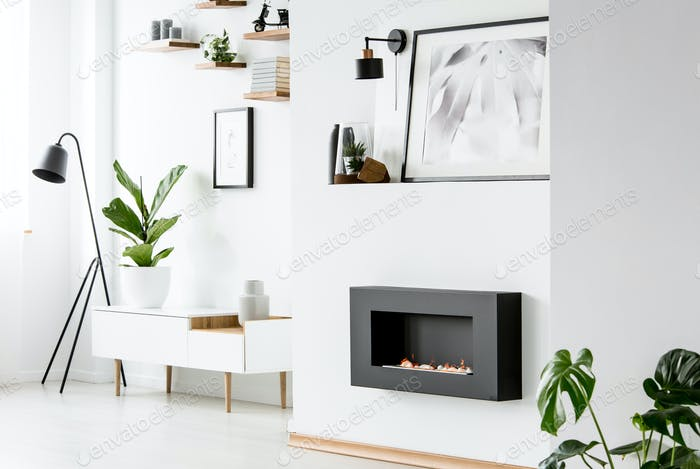 Poster above black fireplace in white apartment interior with pl
