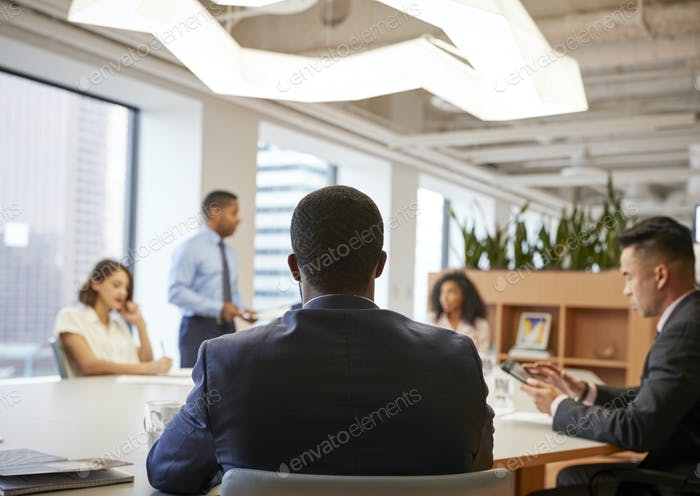 Rear View Of Business Professionals Meeting Around Table In Modern Office