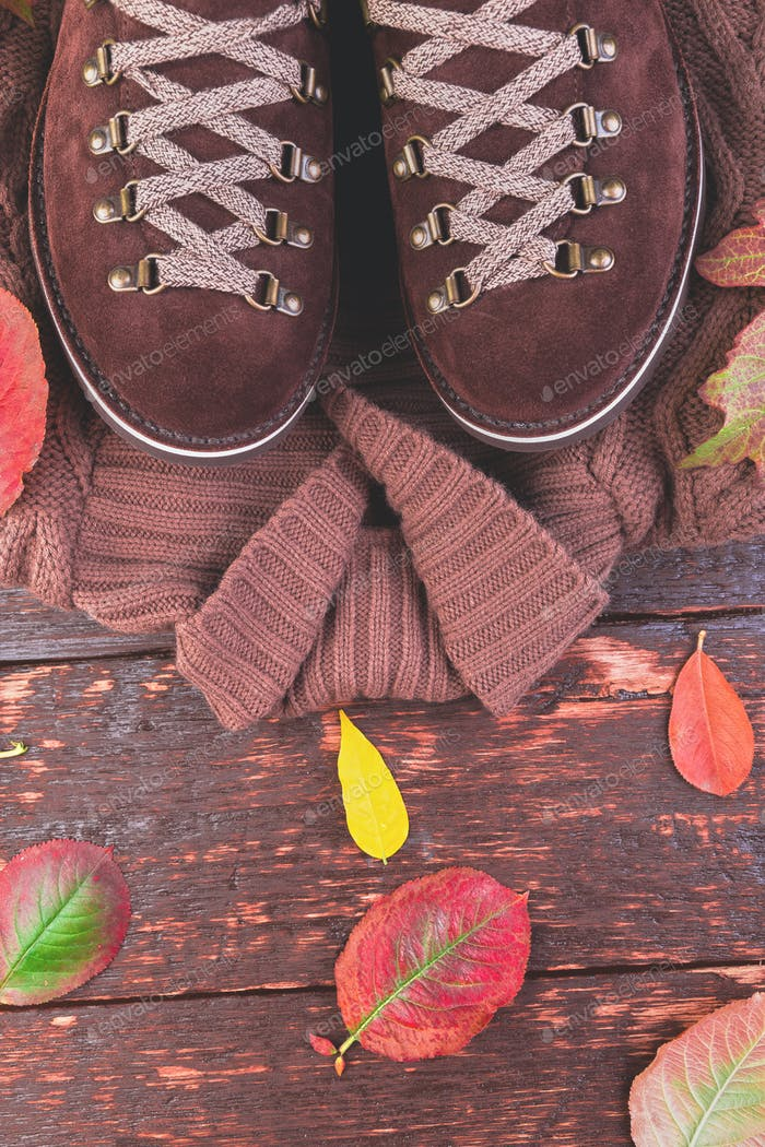 Brown man suede boots with sweater on wooden background
